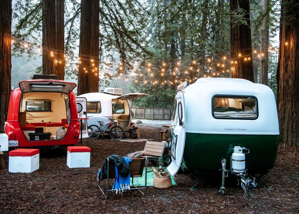 Happier Camper vans in woods under string lights