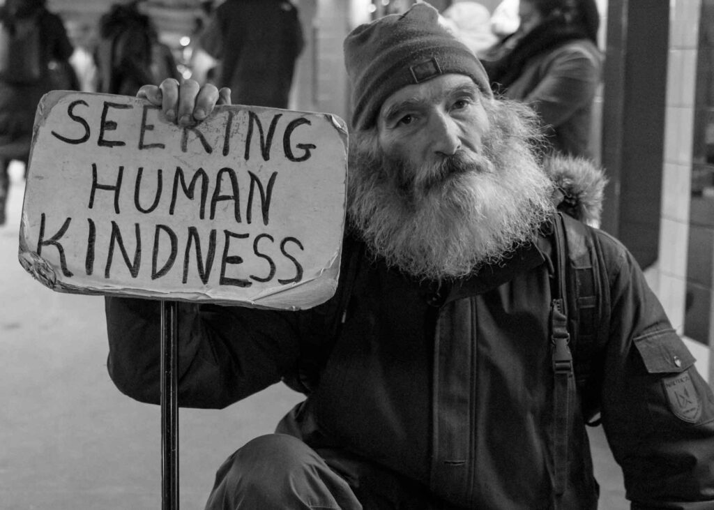 """homeless man with sign that says """"seeking human kindness"""""""