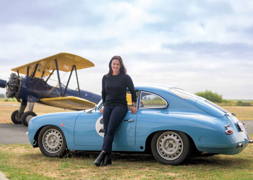 Shannon O'Shaugnessy leaning on a porsche with a plane in the background