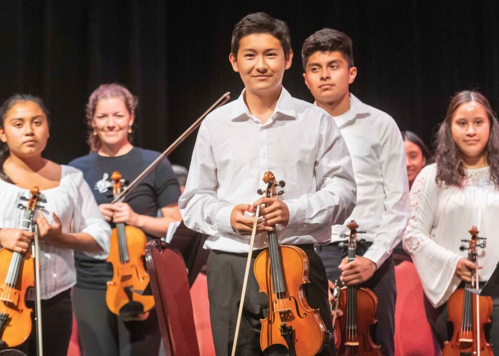 kid musicians smiling with violins
